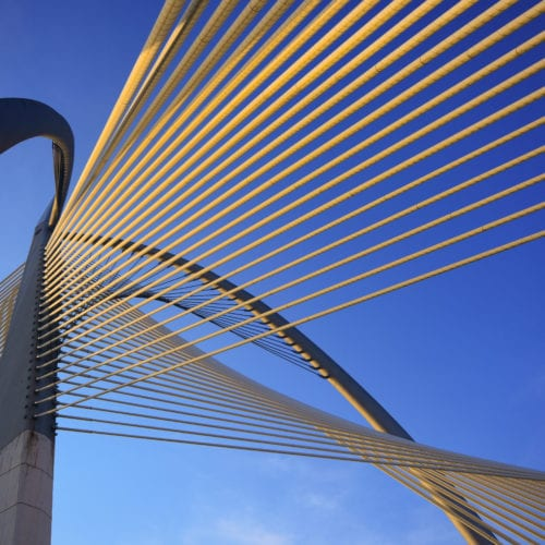 Architectural structure made of wire from perspective of the ground looking into the sky.