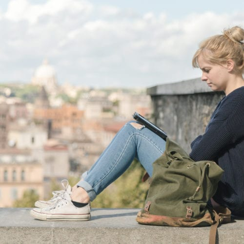 A young woman reading an electronic book outdoors in the park in Rome, Italy.