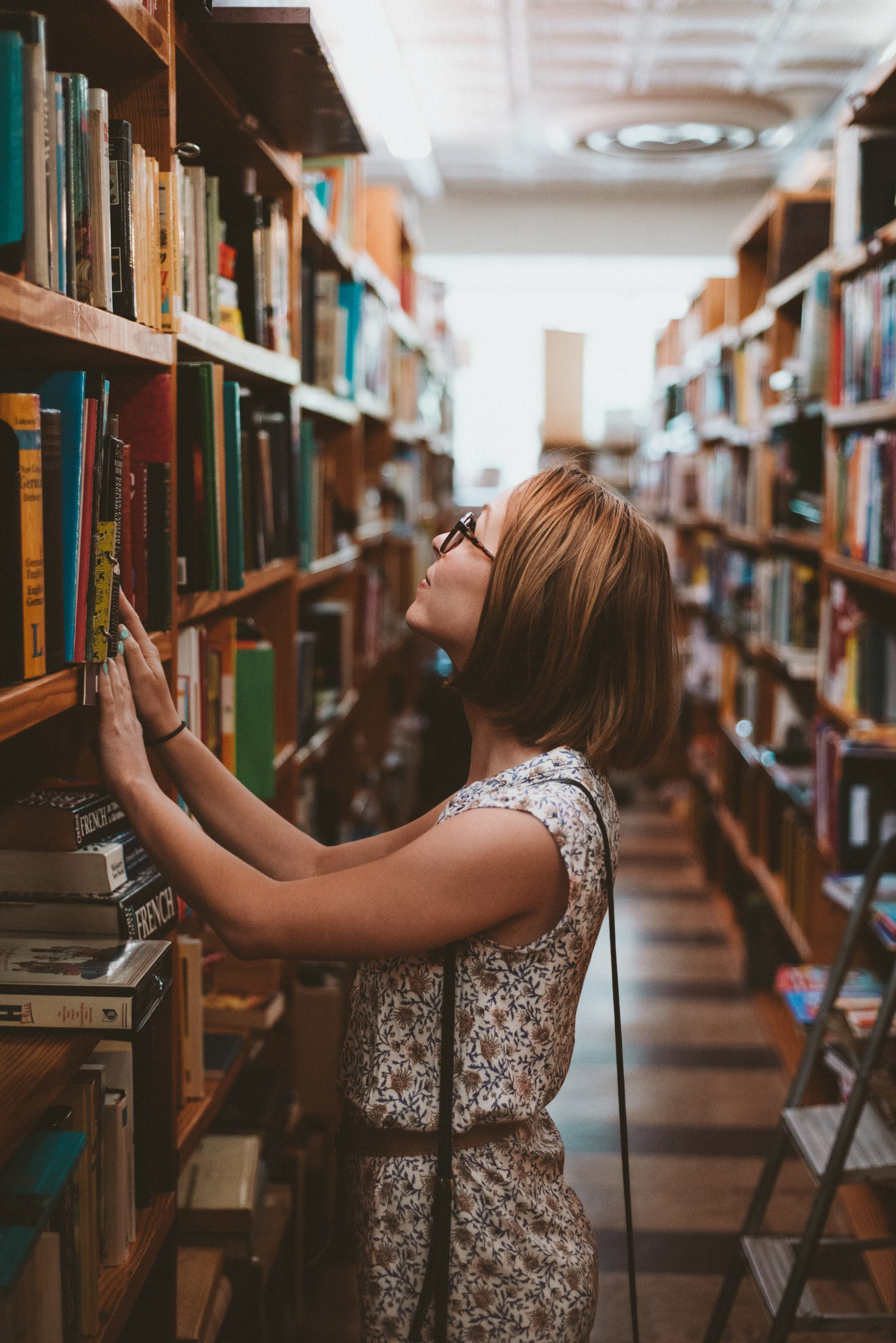 Women in Library looking a books high on the shelf